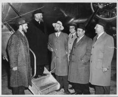 Photograph of Rabbi Eliezer Silver standing on the stairs to an airplane surrounded by other individuals